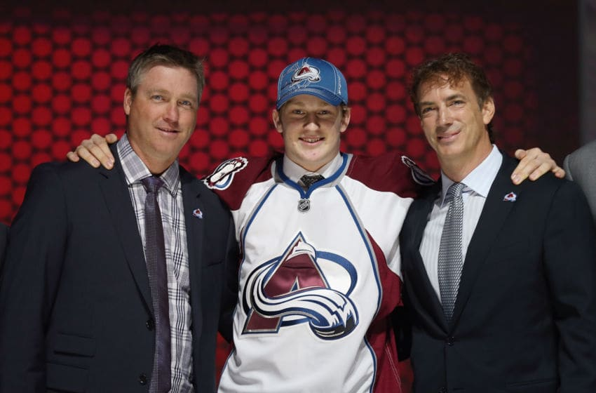 NEWARK, NJ - JUNE 30: Nathan MacKinnon (c) puts on his Colorado Avalanche jersey as he stands with head coach Patrick Roy (l) and Joe Sakic (r) after MacKinnon was selected number one overall in the first round by Colorado during the 2013 NHL Draft at the Prudential Center on June 30, 2013 in Newark, New Jersey. (Photo by Bruce Bennett/Getty Images)