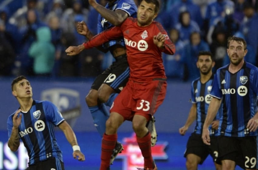 Jun 8, 2016; Montreal, Ontario, Canada; Montreal Impact forward Michael Salazar (19) heads the ball and Toronto FC defender Steven Beitashour (33) defends during the first half at Stade Saputo. Mandatory Credit: Eric Bolte-USA TODAY Sports