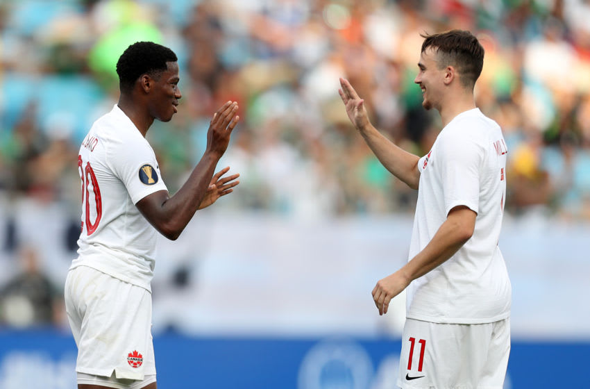 CHARLOTTE, NC - JUNE 23: Jonathan David #20 and Liam Miller #11 of Canada celebrates 6th goal during a group A match between Canada and Cuba at Bank of America Stadium on June 23, 2019 in Charlotte, North Carolina. (Photo by Omar Vega/Getty Images)