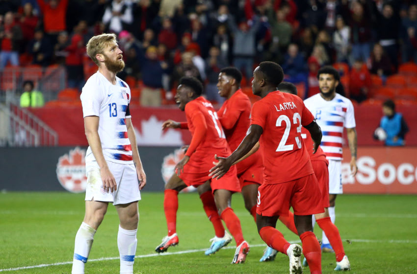 TORONTO, ON - OCTOBER 15: Tim Ream #13 of the United States looks on as Alphonso Davies #12 of Canada celebrates a goal with teammates during a CONCACAF Nations League game at BMO Field on October 15, 2019 in Toronto, Canada. (Photo by Vaughn Ridley/Getty Images)