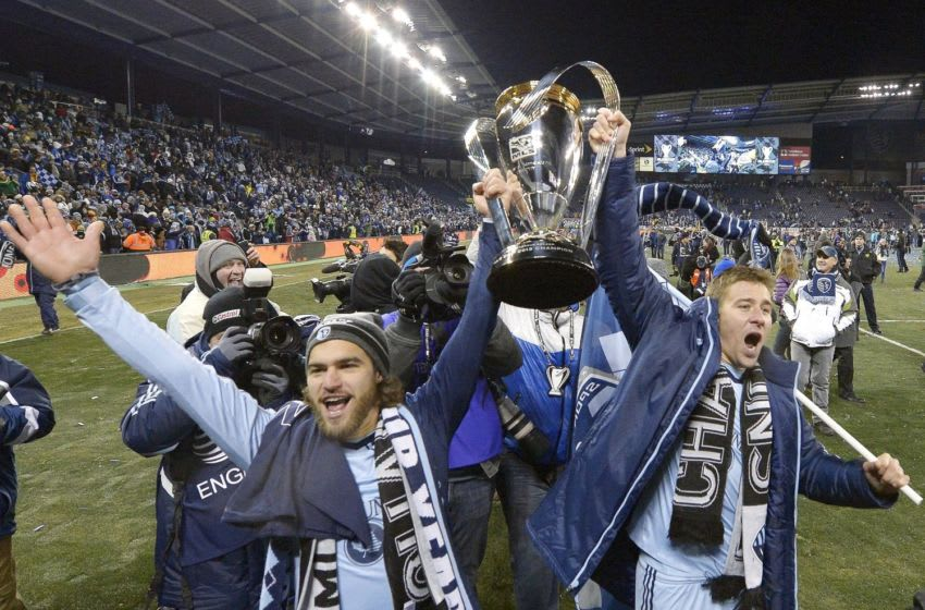 Sporting KC's Graham Zusi and Matt Besler, right, celebrate with the MLS Cup after defeating Real Salt Lake in the MLS Cup Final at Sporting Park in Kansas City, Kan., Saturday, Dec. 7, 2013. Kansas City won on penalty kicks. (John Sleezer/Kansas City Star/Tribune News Service via Getty Images)