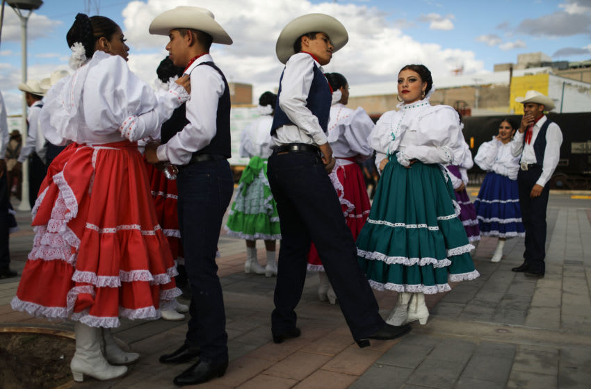 CIUDAD JUAREZ, MEXICO - OCTOBER 14: Traditional dancers prepare to perform during the International Meeting of American Cultures on October 14, 2018 in Ciudad Juarez, Mexico. Ciudad Juarez is a border city which sits directly across the Rio Grande river from El Paso, Texas. (Photo by Mario Tama/Getty Images)