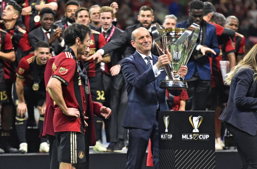 ATLANTA, GA - DECEMBER 08: MLS Commissioner Don Garber (right) lifts the Philip F. Anschutz Trophy to present to Atlanta United owner Arthur Blank (center) and defender Michael Parkhurst (left) after winning the MLS Cup against the Portland Timbers at Mercedes-Benz Stadium in Atlanta, GA. Atlanta won 2-0. (Photo by Austin McAfee/Icon Sportswire via Getty Images)