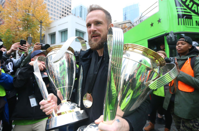 SEATTLE, WASHINGTON - NOVEMBER 12: Stefan Frei #24 of the Seattle Sounders holds his MLS Cup trophies from 2016 and 2019 during their MLS Cup victory parade on November 12, 2019 in Seattle, Washington. (Photo by Abbie Parr/Getty Images)