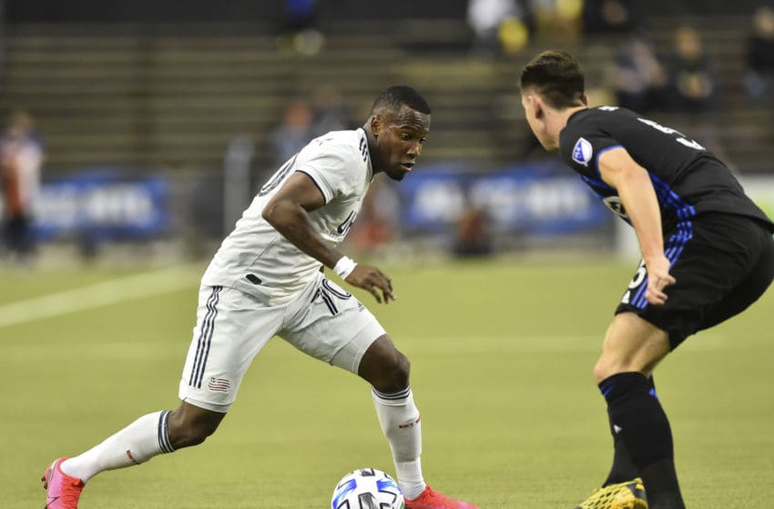 MONTREAL, QC - FEBRUARY 29: Cristian Penilla #70 of New England Revolution controls the ball near Luis Binks #5 of the Montreal Impact in the first half during the MLS game at Olympic Stadium on February 29, 2020 in Montreal, Quebec, Canada. (Photo by Minas Panagiotakis/Getty Images)
