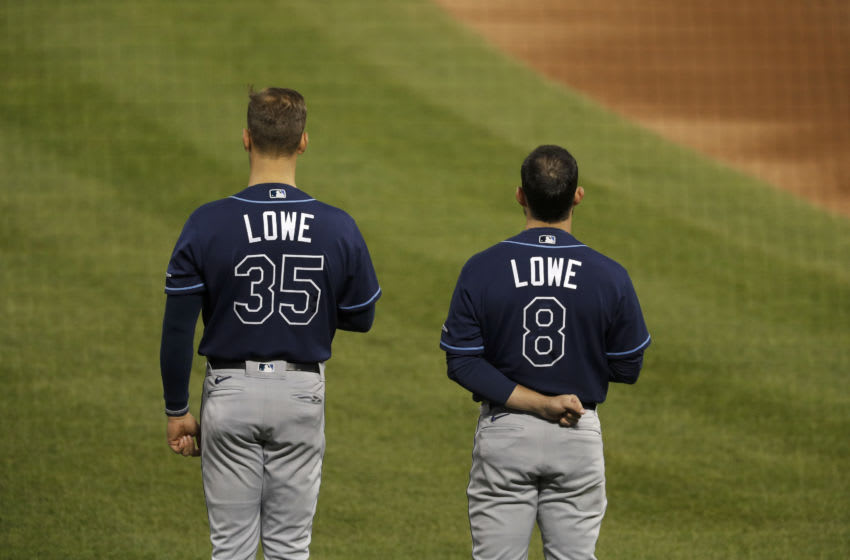 NEW YORK, NEW YORK - SEPTEMBER 22: Nate Lowe #35 and Brandon Lowe #8 of the Tampa Bay Rays stand during the national anthem before a game against the New York Mets at Citi Field on September 22, 2020 in New York City. (Photo by Jim McIsaac/Getty Images)