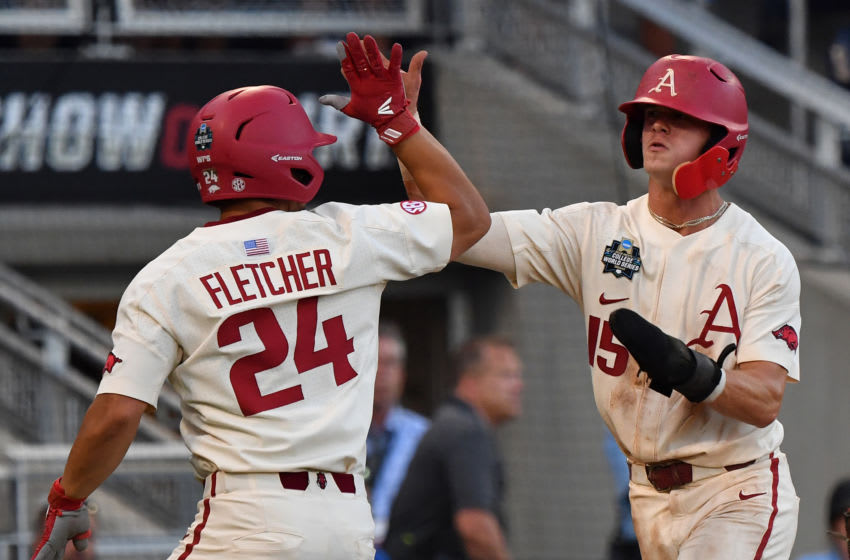 Omaha, NE - JUNE 27: Infielder Casey Martin #15 of the Arkansas Razorbacks celebrates with Outfielder Dominic Fletcher #24 after scoring a run in the fifth inning against the Oregon State Beavers during game two of the College World Series Championship Series on June 27, 2018 at TD Ameritrade Park in Omaha, Nebraska. (Photo by Peter Aiken/Getty Images)