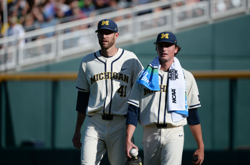 Jun 24, 2019; Omaha, NE, USA; Michigan Wolverines starting pitcher Tommy Henry (47) and Michigan Wolverines pitching coach Chris Fetter (left) walk on the field prior to game one of the championship series of the 2019 College World Series against the Vanderbilt Commodores at TD Ameritrade Park. Mandatory Credit: Steven Branscombe-USA TODAY Sports