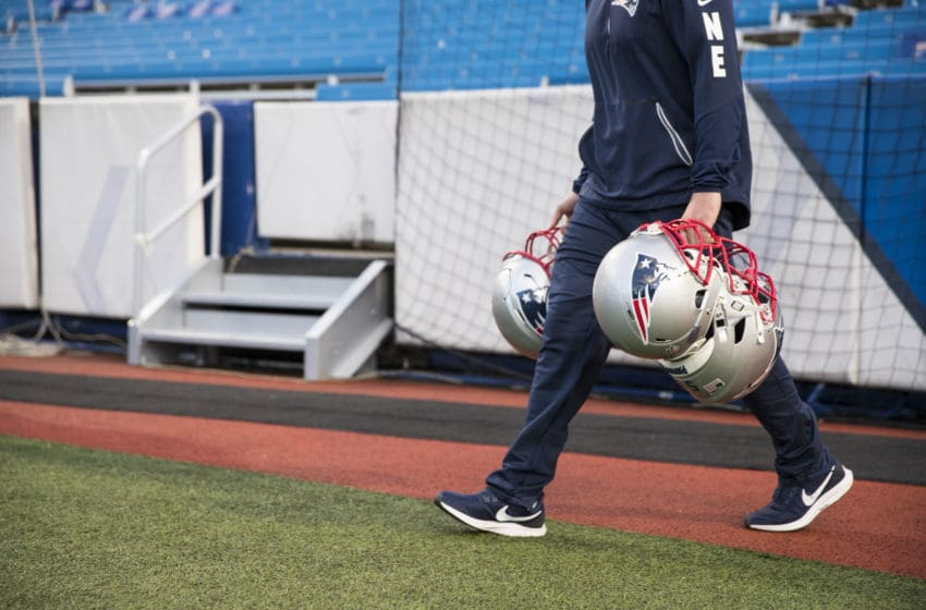 ORCHARD PARK, NY - OCTOBER 29: A equipment personnel member carries New England Patriots helmets to the benches before the game against the Buffalo Bills at New Era Field on October 29, 2018 in Orchard Park, New York. New England defeats Buffalo 25-6. (Photo by Brett Carlsen/Getty Images) *** Local Caption ***