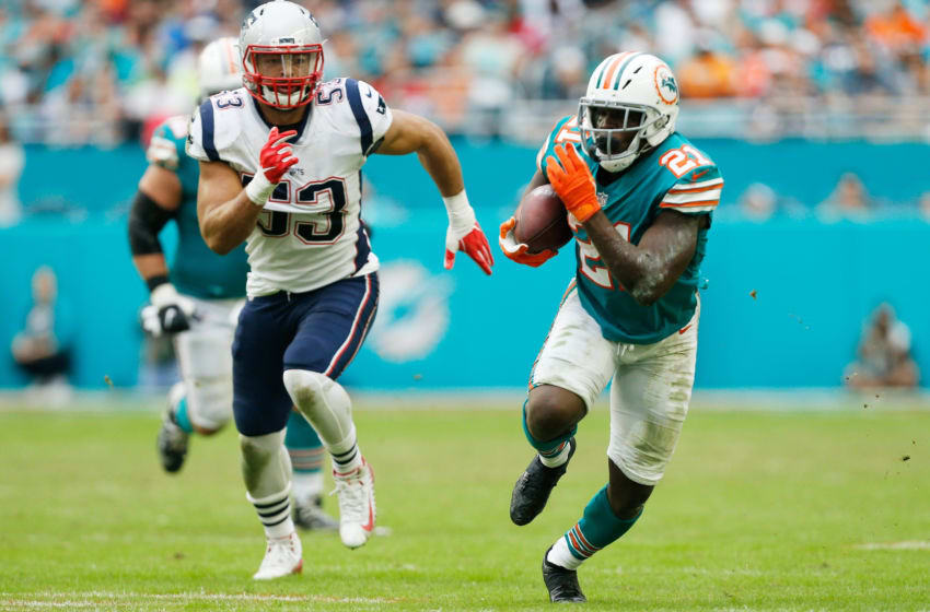 MIAMI, FL - DECEMBER 09: Frank Gore #21 of the Miami Dolphins rushes and avoids the tackle of Kyle Van Noy #53 of the New England Patriots during the second half at Hard Rock Stadium on December 9, 2018 in Miami, Florida. (Photo by Michael Reaves/Getty Images)