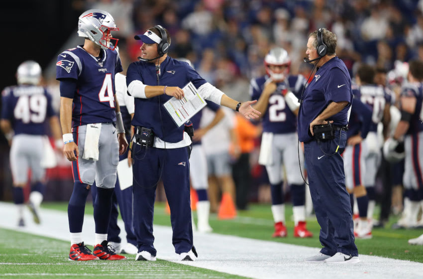 FOXBOROUGH, MASSACHUSETTS - AUGUST 22: Jarrett Stidham #4 of the New England Patriots talks with Offensive Coordinator Josh McDaniels and Head Coach Bill Belichick during the preseason game between the Carolina Panthers and the New England Patriots at Gillette Stadium on August 22, 2019 in Foxborough, Massachusetts. (Photo by Maddie Meyer/Getty Images)