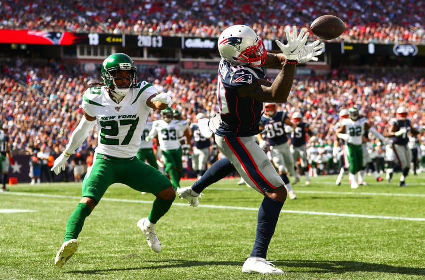 FOXBOROUGH, MA - SEPTEMBER 22: Josh Gordon #10 of the New England Patriots bobbles a throw from Tom Brady #12 of the New England Patriots while under pressure from Darryl Roberts #27 of the New York Jets during a game at Gillette Stadium on September 22, 2019 in Foxborough, Massachusetts. (Photo by Adam Glanzman/Getty Images)