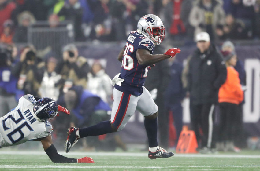 FOXBOROUGH, MASSACHUSETTS - JANUARY 04: Sony Michel #26 of the New England Patriots carries the ball against Logan Ryan #26 of the Tennessee Titans in the first half of the AFC Wild Card Playoff game at Gillette Stadium on January 04, 2020 in Foxborough, Massachusetts. (Photo by Elsa/Getty Images)