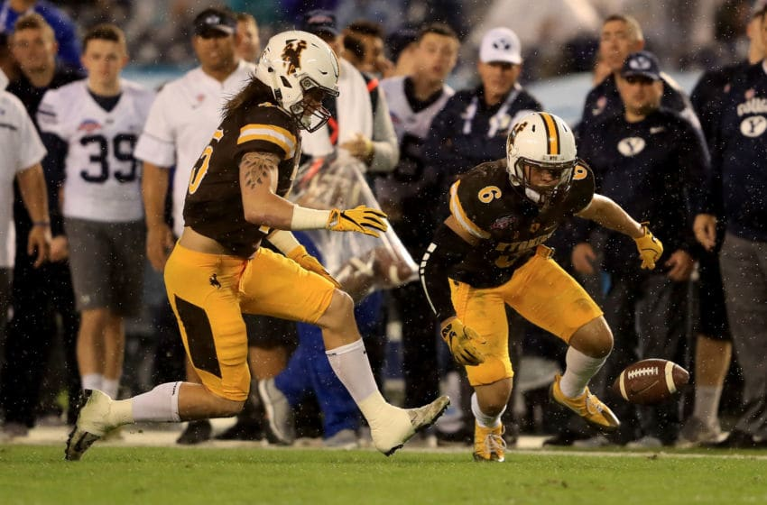 SAN DIEGO, CA - DECEMBER 21: Marcus Epps #6 and Cassh Maluia #46 of the Wyoming Cowboys recover a fumble during the first half of the Poinsettia Bowl at Qualcomm Stadium on December 21, 2016 in San Diego, California. (Photo by Sean M. Haffey/Getty Images)