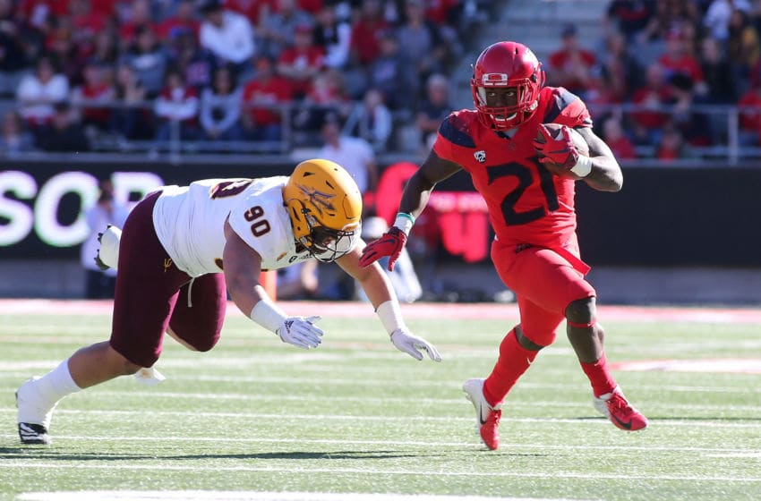 TUCSON, AZ - NOVEMBER 24: Running back J.J. Taylor #21 of the Arizona Wildcats runs the ball as defensive lineman Jermayne Lole #90 of the Arizona State Sun Devils tries to make a tackle during the first half of the college football game at Arizona Stadium on November 24, 2018 in Tucson, Arizona. (Photo by Ralph Freso/Getty Images)