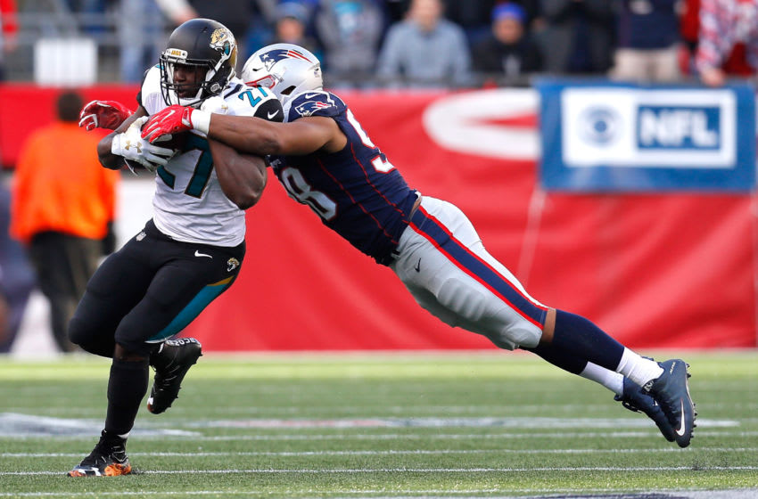 Leonard Fournette #27 of the Jacksonville Jaguars carries the ball as he is defended by Trey Flowers #98 of the New England Patriots in the first quarter during the AFC Championship Game at Gillette Stadium on January 21, 2018 in Foxborough, Massachusetts. (Photo by Kevin C. Cox/Getty Images)