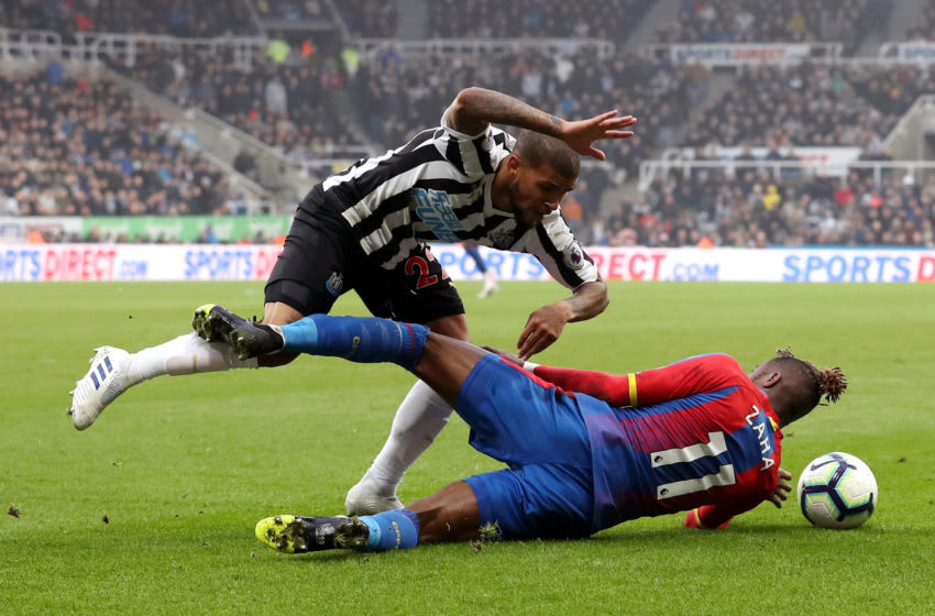 NEWCASTLE UPON TYNE, ENGLAND - APRIL 06: Deandre Yedlin of Newcastle United is tackled by Wilfried Zaha of Crystal Palace during the Premier League match between Newcastle United and Crystal Palace at St. James Park on April 06, 2019 in Newcastle upon Tyne, United Kingdom. (Photo by Ian MacNicol/Getty Images)