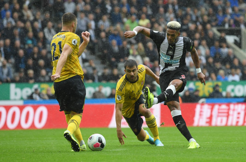 NEWCASTLE UPON TYNE, ENGLAND - AUGUST 11: Joelinton of Newcastle United shoots for goal under pressure from Sokratis Papastathopoulos and Calum Chambers of Arsenal during the Premier League match between Newcastle United and Arsenal FC at St. James Park on August 11, 2019 in Newcastle upon Tyne, United Kingdom. (Photo by Stu Forster/Getty Images)