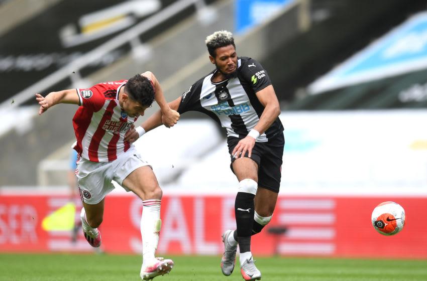 John Egan of Sheffield United pulls the shirt of Joelinton of Newcastle United. (Photo by Michael Regan/Getty Images)