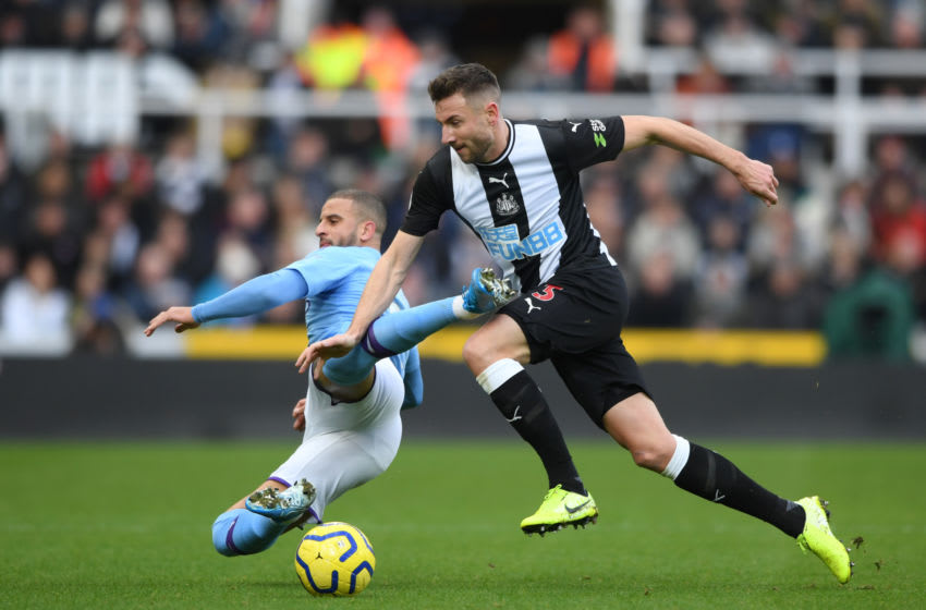 Kyle Walker of Manchester City is tackled by Paul Dummett of Newcastle United. (Photo by Stu Forster/Getty Images)