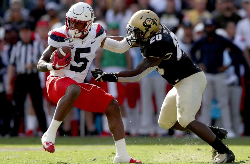 BOULDER, COLORADO - OCTOBER 05: Brian Casteel #5 of the Arizona Wildcats tries to break free from Davion Taylor #20 of the Colorado Buffaloes in the second quarter at Folsom Field on October 05, 2019 in Boulder, Colorado. (Photo by Matthew Stockman/Getty Images)