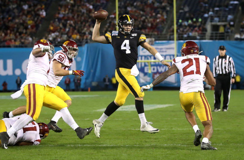SAN DIEGO, CALIFORNIA - DECEMBER 27: Nate Stanley #4 of the Iowa Hawkeyes eludes the defense of Marlon Tuipulotu #51, and Isaiah Pola-Mao #21 of the USC Trojans during the second half of the San Diego County Credit Union Holiday Bowl at SDCCU Stadium on December 27, 2019 in San Diego, California. (Photo by Sean M. Haffey/Getty Images)