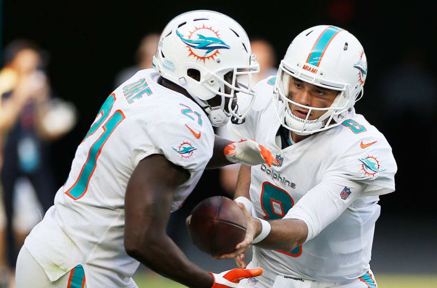 MIAMI, FL - OCTOBER 14: Brock Osweiler #8 of the Miami Dolphins hands off to Frank Gore #21 in the fourth quarter against the Chicago Bears at Hard Rock Stadium on October 14, 2018 in Miami, Florida. (Photo by Marc Serota/Getty Images)