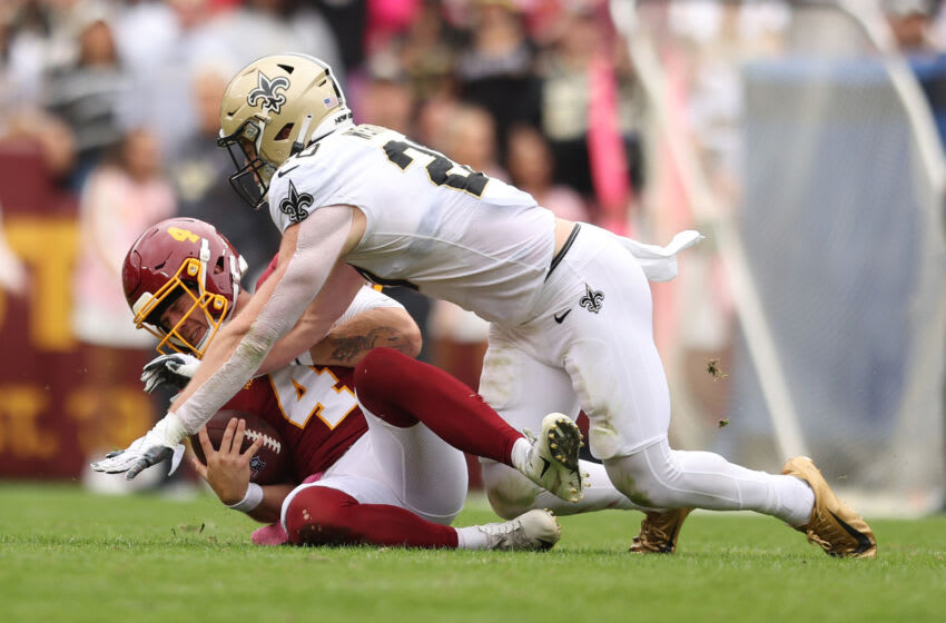 LANDOVER, MARYLAND - OCTOBER 10: Taylor Heinicke #4 of the Washington Football Team is sacked by Pete Werner #20 of the New Orleans Saints during the first half at FedExField on October 10, 2021 in Landover, Maryland. (Photo by Patrick Smith/Getty Images)