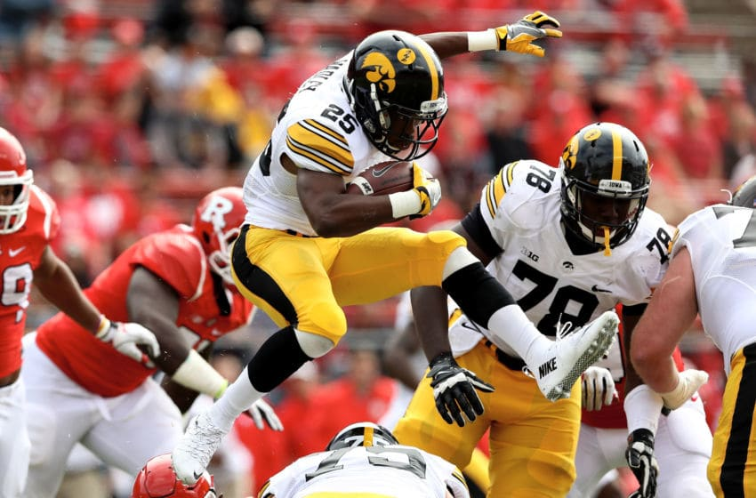 PISCATAWAY, NJ - SEPTEMBER 24: Akrum Wadley #25 of the Iowa Hawkeyes leaps over teammate Ike Boettger #75 as he carries the ball in the first half against the Rutgers Scarlet Knights at High Point Solutions Stadium on September 24, 2016 in Piscataway, New Jersey. (Photo by Elsa/Getty Images)