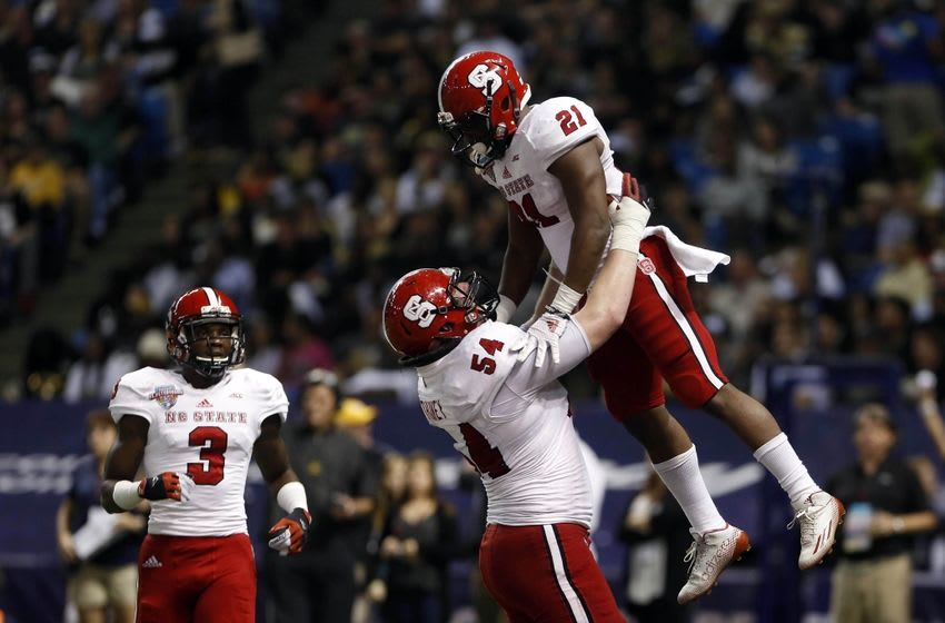 Dec 26, 2014; St. Petersburg, FL, USA; North Carolina State Wolfpack running back Matt Dayes (21) and guard Joe Thuney (54) celebrate during the game against the Central Florida Knights at the 2014 St. Petersburg Bowl at Tropicana Field. The North Carolina State Wolfpack defeated the Central Florida Knights 34-27. Mandatory Credit: Mark Zerof-USA TODAY Sports