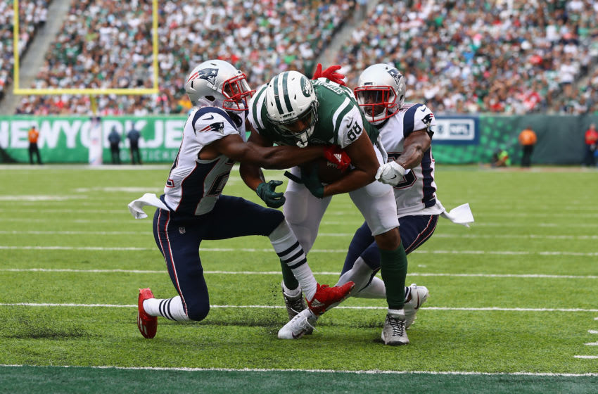 EAST RUTHERFORD, NJ - OCTOBER 15: Tight end Austin Seferian-Jenkins #88 of the New York Jets runs the ball for what was originally called a touchdown against strong safety Duron Harmon #30 and cornerback Malcolm Butler #21 of the New England Patriots during the fourth quarter of their game at MetLife Stadium on October 15, 2017 in East Rutherford, New Jersey. The Replay Official reviewed the runner broke the plane ruling, and the play was reversed and called a fumble. (Photo by Al Bello/Getty Images)