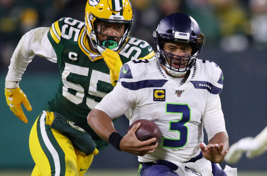GREEN BAY, WISCONSIN - JANUARY 12: Russell Wilson #3 of the Seattle Seahawks runs with the ball against Za'Darius Smith #55 of the Green Bay Packers during the second half in the NFC Divisional Playoff game at Lambeau Field on January 12, 2020 in Green Bay, Wisconsin. (Photo by Gregory Shamus/Getty Images)
