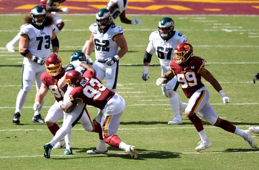LANDOVER, MD - SEPTEMBER 13: Matthew Ioannidis #98, Jonathan Allen #93 and Chase Young #99 of the Washington Football Team tackle Carson Wentz #11 of the Philadelphia Eagles in the second half at FedExField on September 13, 2020 in Landover, Maryland. (Photo by G Fiume/Getty Images)