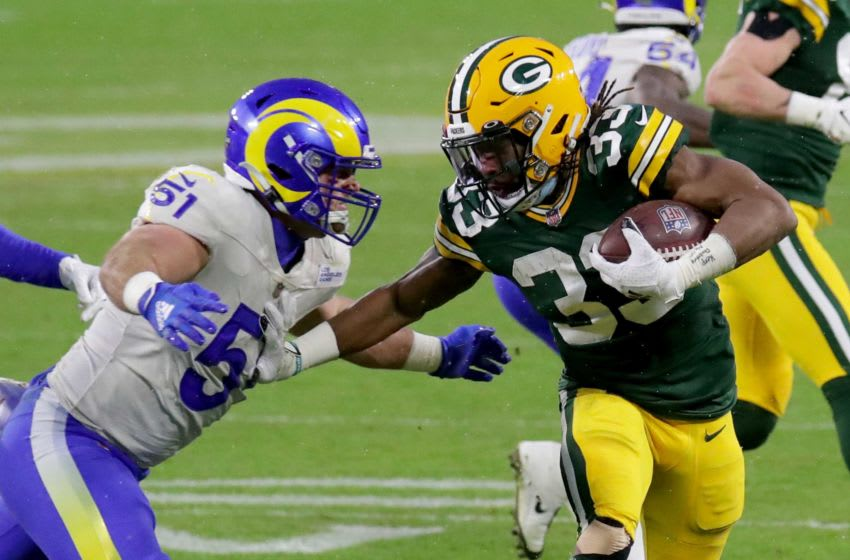 Green Bay Packers running back Aaron Jones (33) rushes for a gain past Los Angeles Rams inside linebacker Troy Reeder (51) during the 2nd quarter of the Green Bay Packers Los Angeles Rams NFC divisional playoff game Saturday, Jan. 16, 2021, at Lambeau Field in Green Bay, Wis. Packers Rams 03157