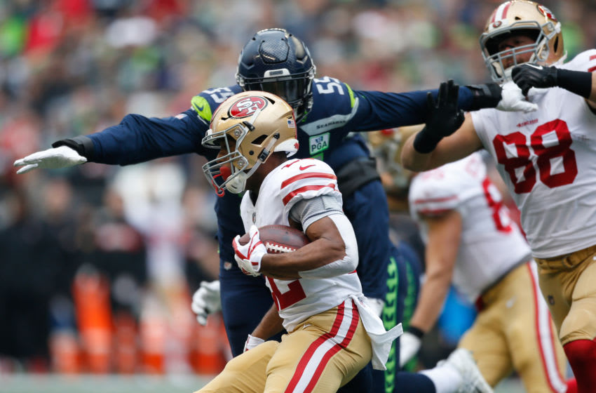 SEATTLE, WA - DECEMBER 02: Frank Clark #55 of the Seattle Seahawks attempts to tacks Matt Breida #22 of the San Francisco 49ers in the first quarter at CenturyLink Field on December 2, 2018 in Seattle, Washington. (Photo by Otto Greule Jr/Getty Images)