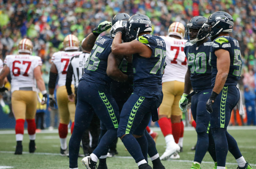 SEATTLE, WA - SEPTEMBER 17: Defensive end Frank Clark #55 of the Seattle Seahawks, left, celebrates sacking quarterback Brian Hoyer #2 of the San Francisco 49ers with teammates, including defensive end Michael Bennett #72 during the third quarter of the game at CenturyLink Field on September 17, 2017 in Seattle, Washington. (Photo by Otto Greule Jr /Getty Images)