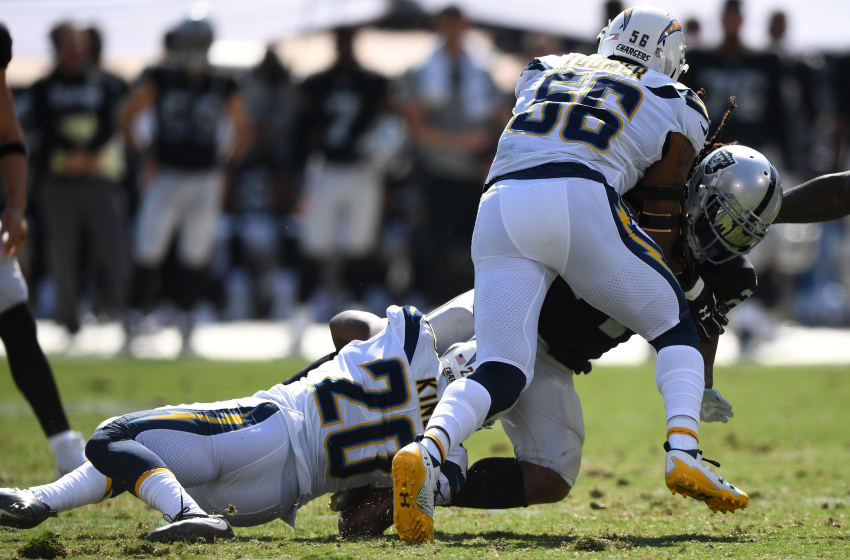 OAKLAND, CA - OCTOBER 15: Marshawn Lynch #24 of the Oakland Raiders is tackled by Desmond King #20 and Korey Toomer #56 of the Los Angeles Chargers during their NFL game at Oakland-Alameda County Coliseum on October 15, 2017 in Oakland, California. (Photo by Thearon W. Henderson/Getty Images)