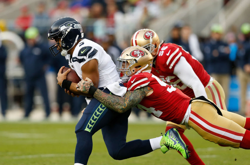 SANTA CLARA, CA - NOVEMBER 26: Quarterback Russell Wilson #75 of the Seattle Seahawks is tackled by Cassius Marsh #54 of the San Francisco 49ers at Levi's Stadium on November 26, 2017 in Santa Clara, California. (Photo by Lachlan Cunningham/Getty Images)