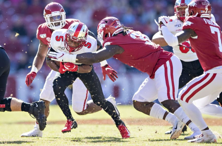 FAYETTEVILLE, AR - NOVEMBER 9: Gaej Walker #5 of the Western Kentucky Hilltoppers runs the ball and is tackled by McTelvin Agim #3 of the Arkansas Razorbacks at Razorback Stadium on November 9, 2019 in Fayetteville, Arkansas. The Hilltoppers defeated the Razorbacks 45-19. (Photo by Wesley Hitt/Getty Images)