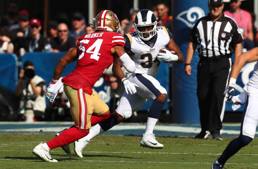 Malcolm Brown #34 of the Los Angeles Rams tries to outrun Fred Warner #54 of the San Francisco 49ers (Photo by Joe Scarnici/Getty Images)