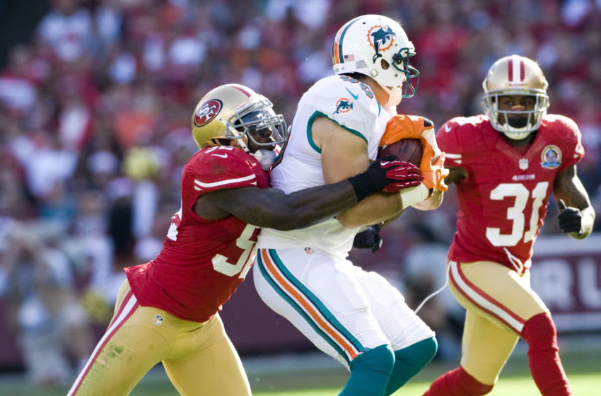 Patrick Willis #52 and Donte Whitner #31 of the San Francisco 49ers tackle Anthony Fasano #80 of the Miami Dolphins (Photo by Michael Zagaris/San Francisco 49ers/Getty Images)