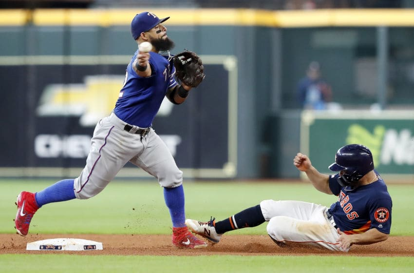 HOUSTON, TX - JULY 21: Rougned Odor #12 of the Texas Rangers throws to first to complete a double play while avoiding a slide by Jose Altuve #27 of the Houston Astros in the seventh inning at Minute Maid Park on July 21, 2019 in Houston, Texas. (Photo by Tim Warner/Getty Images)