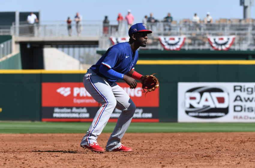 GOODYEAR, ARIZONA - FEBRUARY 24: Sherten Apostel #82 of the Texas Rangers gets ready to make a play at third base during a spring training game against the Cincinnati Reds at Goodyear Ballpark on February 24, 2020 in Goodyear, Arizona. (Photo by Norm Hall/Getty Images)