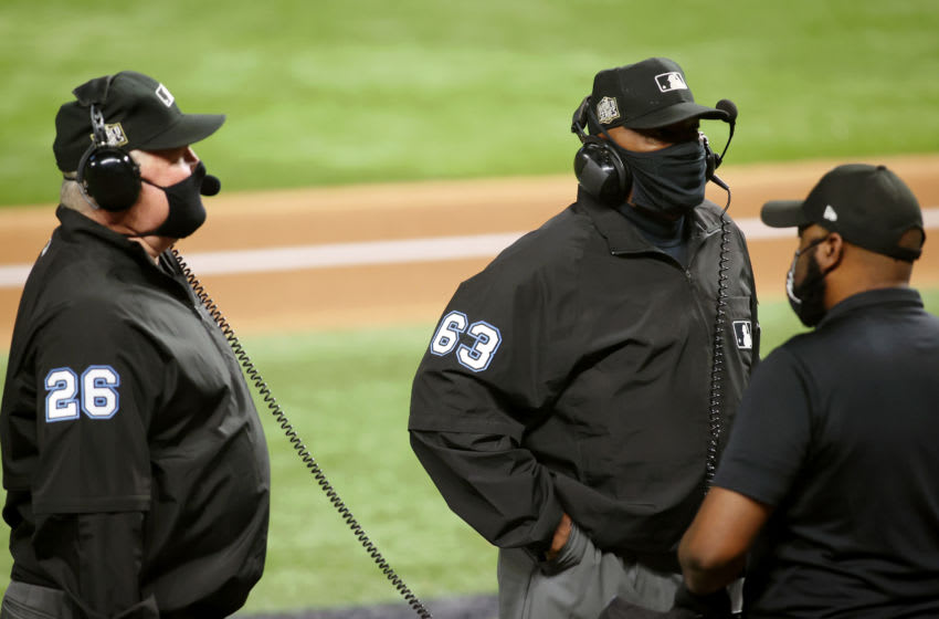 Oct 25, 2020; Arlington, Texas, USA; Left field umpire Bill Miller (26) and second base umpire Laz Diaz (63) during a video review of a play during the first inning during game five of the 2020 World Series between the Los Angeles Dodgers and the Tampa Bay Rays at Globe Life Field. Mandatory Credit: Tim Heitman-USA TODAY Sports