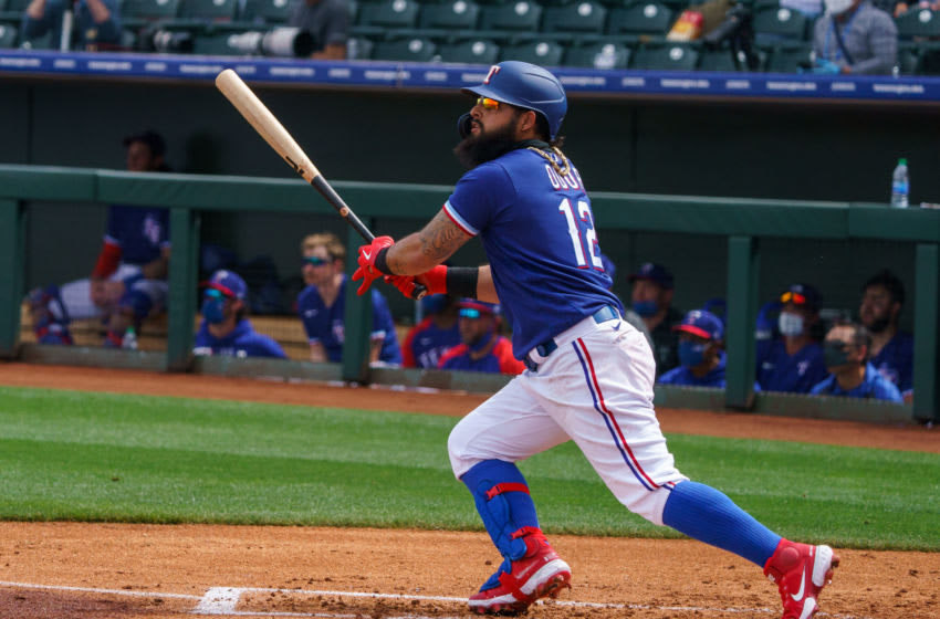 Mar 7, 2021; Surprise, Arizona, USA; Texas Ranger infielder Rougned Odor (12) hits a home run in the first inning against the Los Angeles Dodgers at Surprise Stadium. Mandatory Credit: Allan Henry-USA TODAY Sports