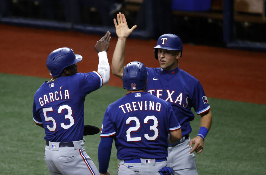 Apr 13, 2021; St. Petersburg, Florida, USA; Texas Rangers outfielder Adolis Garc'a (53) and catcher Jose Trevino (23) and first baseman Nate Lowe (facing camera) react after scoring against the Tampa Bay Rays during the fourth inning at Tropicana Field. Mandatory Credit: Kim Klement-USA TODAY Sports