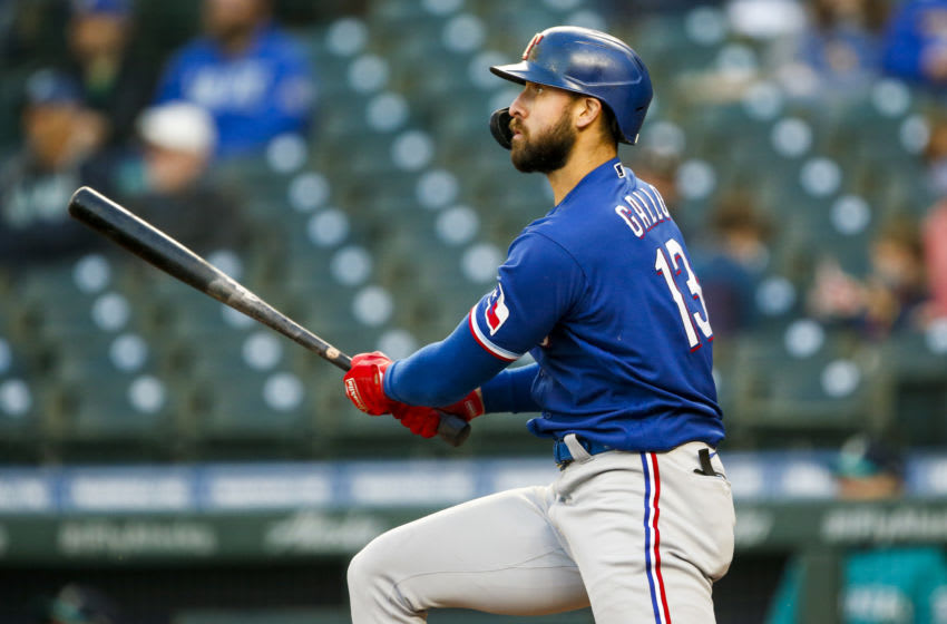 May 28, 2021; Seattle, Washington, USA; Texas Rangers right fielder Joey Gallo (13) hits a double against the Seattle Mariners during the fourth inning at T-Mobile Park. Mandatory Credit: Joe Nicholson-USA TODAY Sports