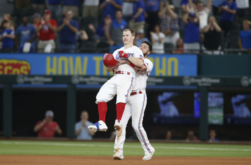 Jun 9, 2021; Arlington, Texas, USA; Texas Rangers third baseman Brock Holt (16) is congratulated by shortstop Isiah Kiner-Falefa (9) after driving in the winning run in the eleventh inning against the San Francisco Giants at Globe Life Field. Mandatory Credit: Tim Heitman-USA TODAY Sports