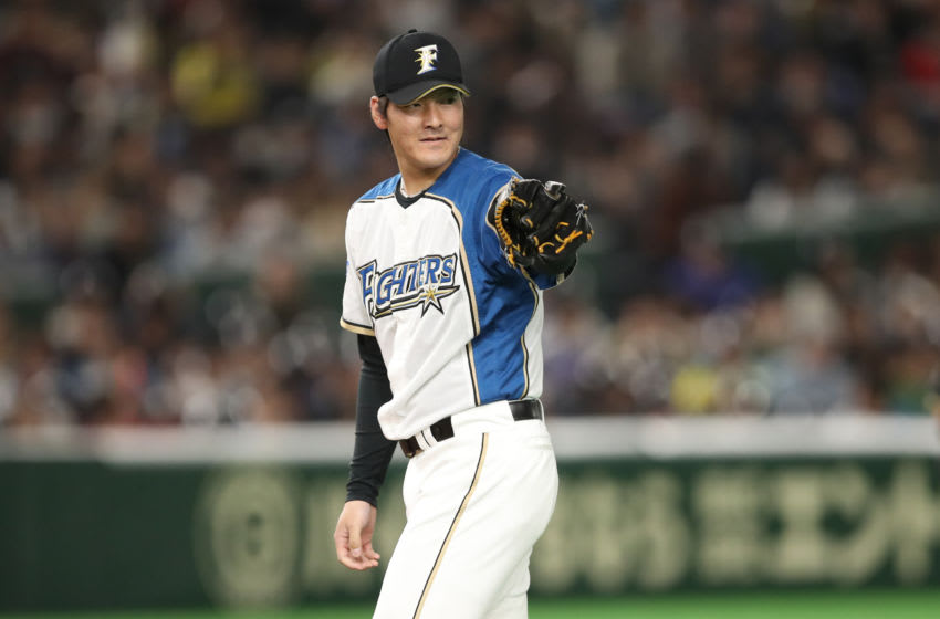 Mar 17, 2019; Tokyo, Japan; Nippon Ham Fighters pitcher Kohei Arihara (16) gestures towards first base before the first pitch of the game against the Oakland Athletics at Tokyo Dome. Mandatory Credit: Darren Yamashita-USA TODAY Sports