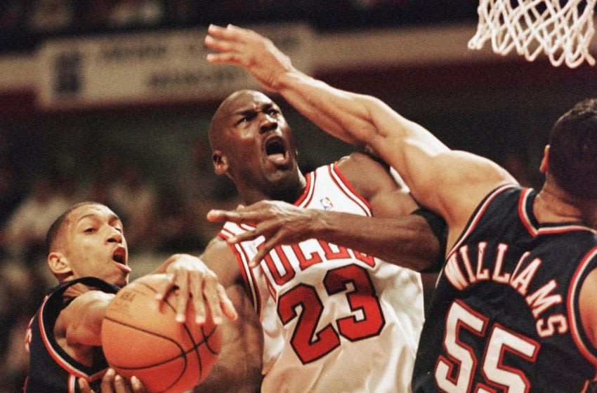 CHICAGO, UNITED STATES: Michael Jordan (C) of the Chicago Bulls drives to the basket past Kerry Kittles (L) and Jayson Williams (R) of the New Jersey Nets 24 April during the second half of their first round play-off game at the United Center in Chicago, IL. The Bulls won the 96-93 in overtime to take a 1-0 lead in the five game series. AFP PHOTO/Jeff HAYNES (Photo credit should read JEFF HAYNES/AFP via Getty Images)